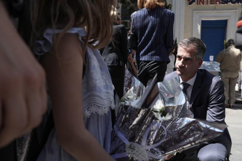 Ο Κώστας Μπακογιάννης, γονατιστός μιλά με συγγενείς θυμάτων στην τελετή μνήμης της Marfin