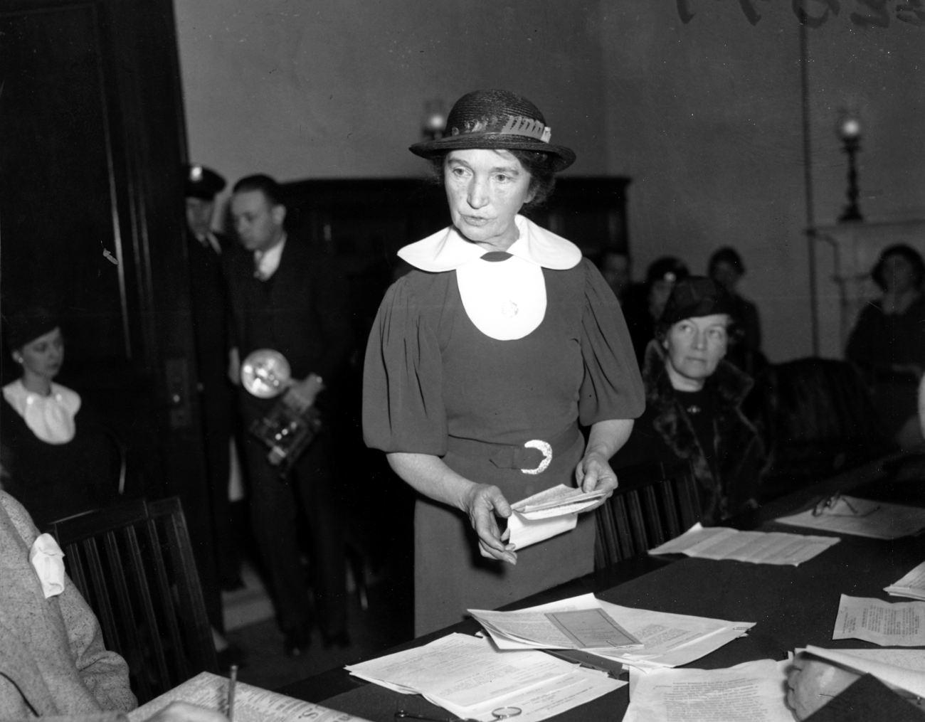 Η Μάργκαρετ Σέινγκερ σε με καπέλο και φαρδύ γιακά σε ασπρόμαυρη φωτογραφία