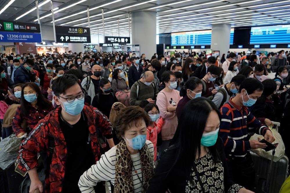 Επιβάτες με μάσκες σε αίθουσα αεροδρομίου