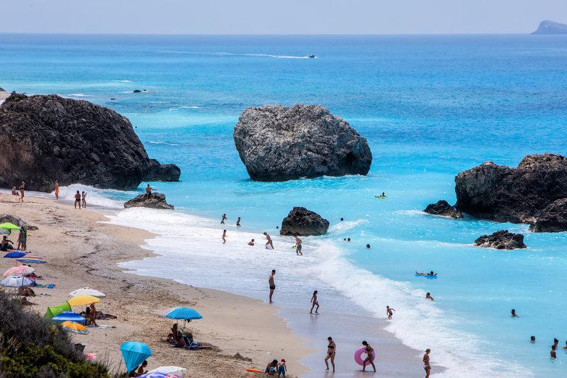 Τουρίστες απολαμβάνουν το μπάνιο τους στην παραλία Μεγάλη Πέτρα