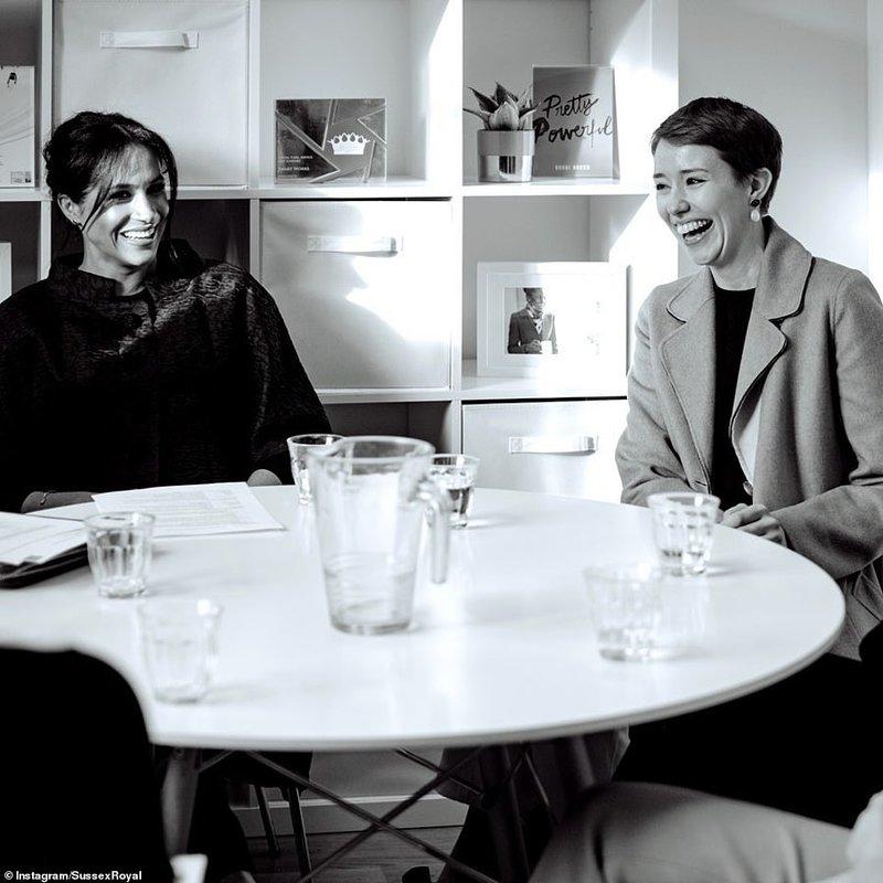 Η έγκυος Μέγκαν Μαρκλ κάθεται σε τραπέζι και χαμογελά
