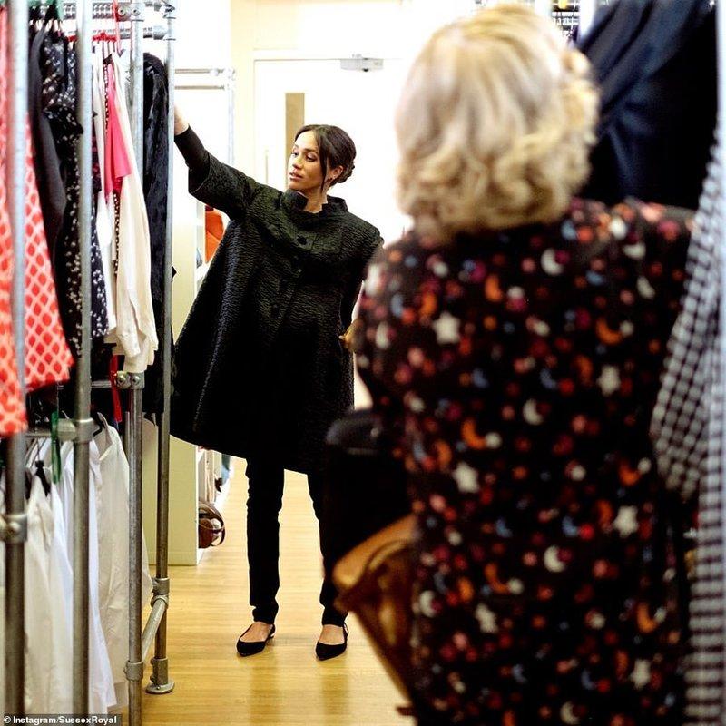Η Μέγκαν Μαρκλ μπροστά σε κρεμαστές με ρούχα