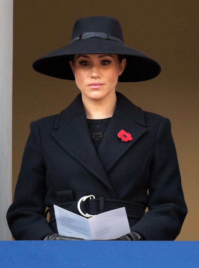 Η Μέγκαν Μαρκλ με μαύρο καπέλο και μαύρο παλτό και δραματικό ύφος