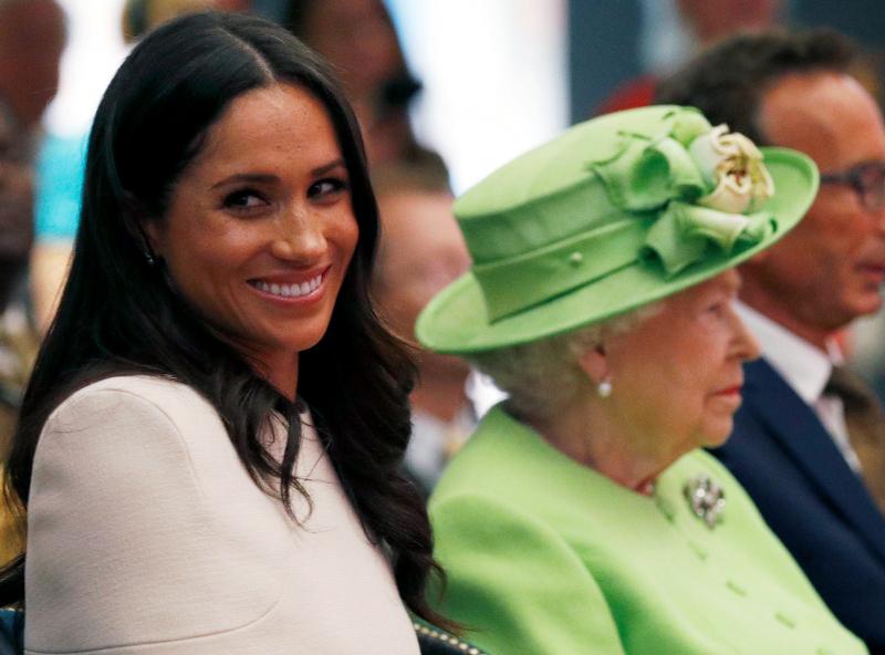 Μέγκαν Μαρκλ χαμογελαστή και πίσω η βασίλισσα Ελισάβετ
