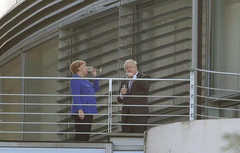 Μέρκελ και Τζόνσον συζητούν πίνοντας στο μπαλκόκι του γραφείου της Καγκελαρίου