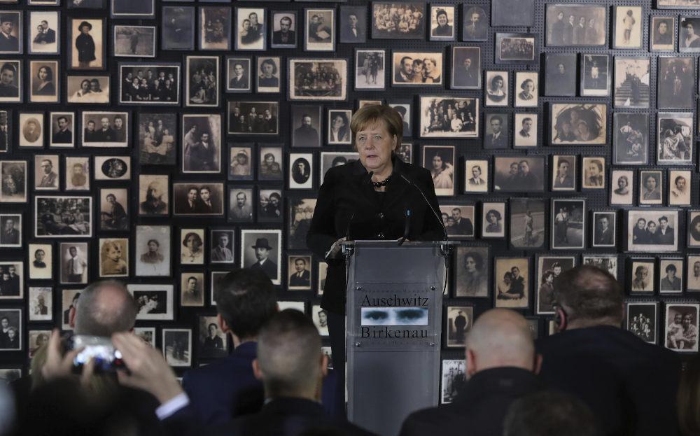 Η εικόνα της Άνγκελα Μέρκελ μπροστά από τον τοίχο με τις φωτογραφίες θυμάτων του Άουσβιτς στην αίθουσα «Σάουνα»