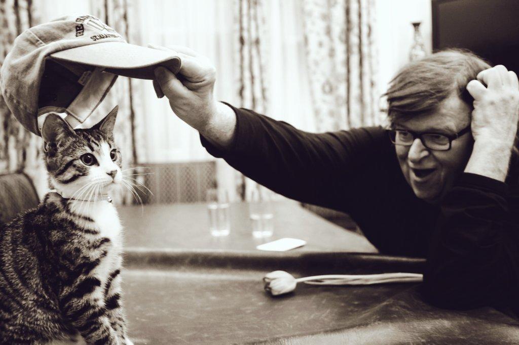 Ασπρόμαυρη φωτογραφία του Μάικλ Μουρ να βάζει καπέλο στο γάτο της πρεσβείας