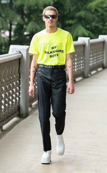 Αντρας με κίτρινη μπλούζα και μαύρο παντελόνι