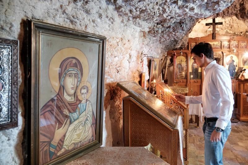 Ο Ο γιος του Κυριάκου Μητσοτάκη, Κωνσταντίνος ανάβει κερί