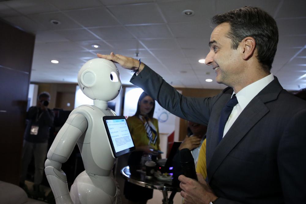 Ο Κυριάκος Μητσοτάκης χαμογελά και χαϊδεύει το ρομπότ στο συνέδριο Digital Economy Forum