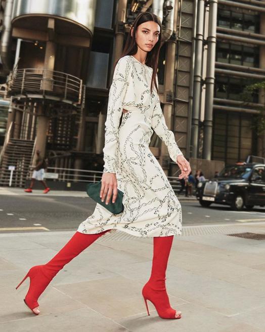 Μοντέλο της Βικτόρια Μπέκαμ με κόκκινες μπότες και λευκό φόρεμα με αλυσίδες