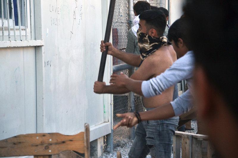 Μετανάστης κρατάει ξύλο