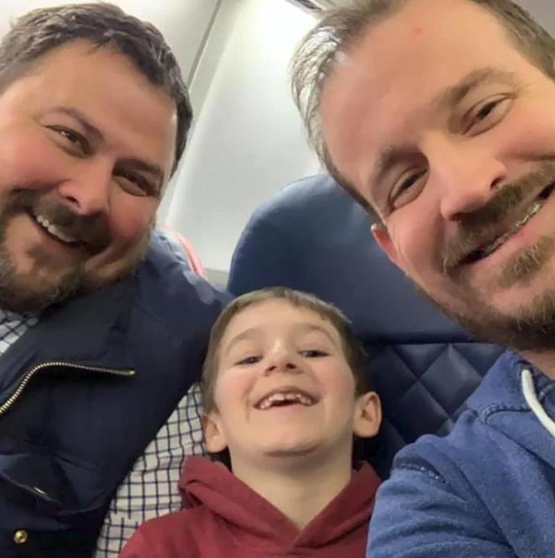 Οι δύο μπαμπάδες χαμογελαστοί με τον χαρούμενο γιο τους