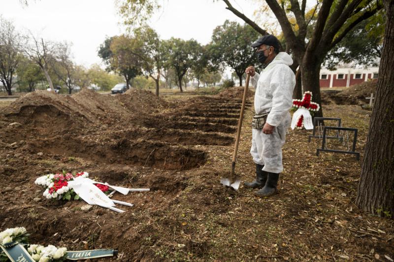 Υπάλληλος με ειδική προστατευτική στολή και μάσκα ετοιμάζεται να κλείσει έναν τάφο θύματος κορωνοϊού