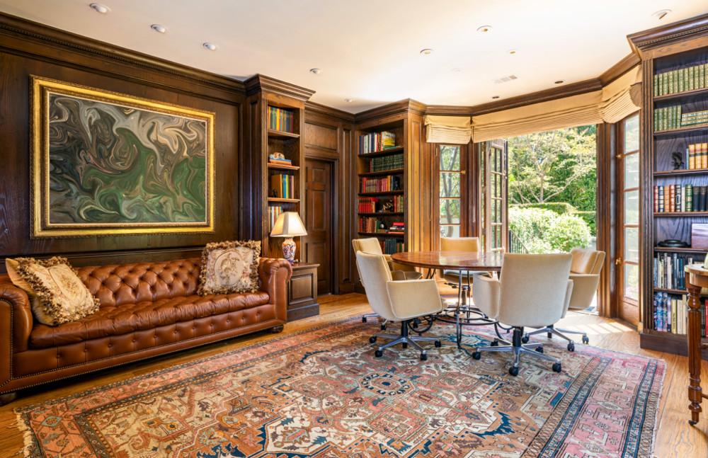 γραφείο  με έναν καφέ δερμάτινο καναπέ να δεσπόζει στο κέντρο του δωματίου και έναν εντυπωσιακό πίνακα