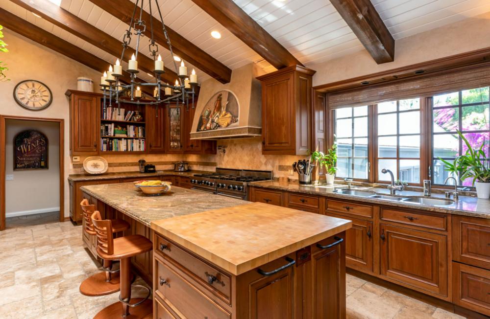 Η κουζίνα της έπαυλης με τους γρανιτένιους πάγκους και την επικλινή οροφή με τα ορατά δοκάρια