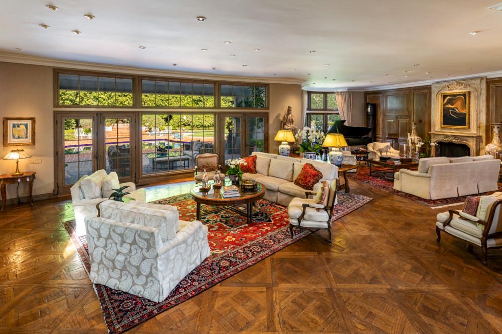 Το τεράστιο σαλόνι με τους μπεζ καναπέδες και θέα την πισίνα
