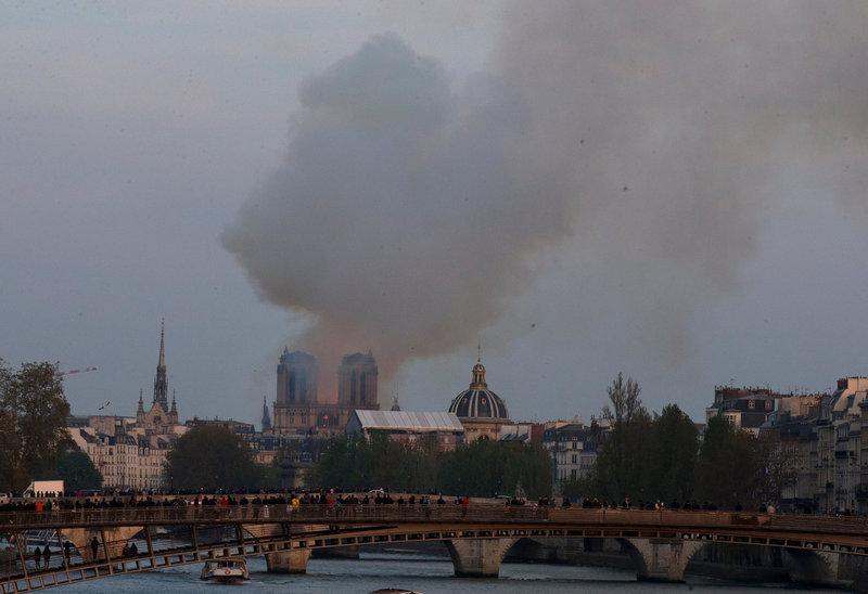 Πυκνό σύννεφο καπνού από την Παναγία των Παρισίων, όπως φαίνεται από τον Σηκουάνα -Φωτογραφία: AP