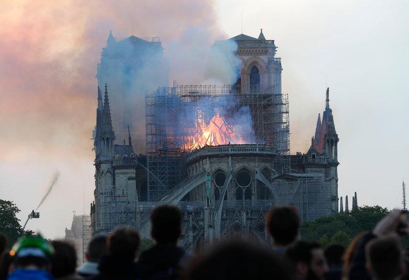 Κόσμος παρακολουθεί με θλίψη την πυρκαγιά στην Νότρ Νταμ -Φωτογραφία: AP