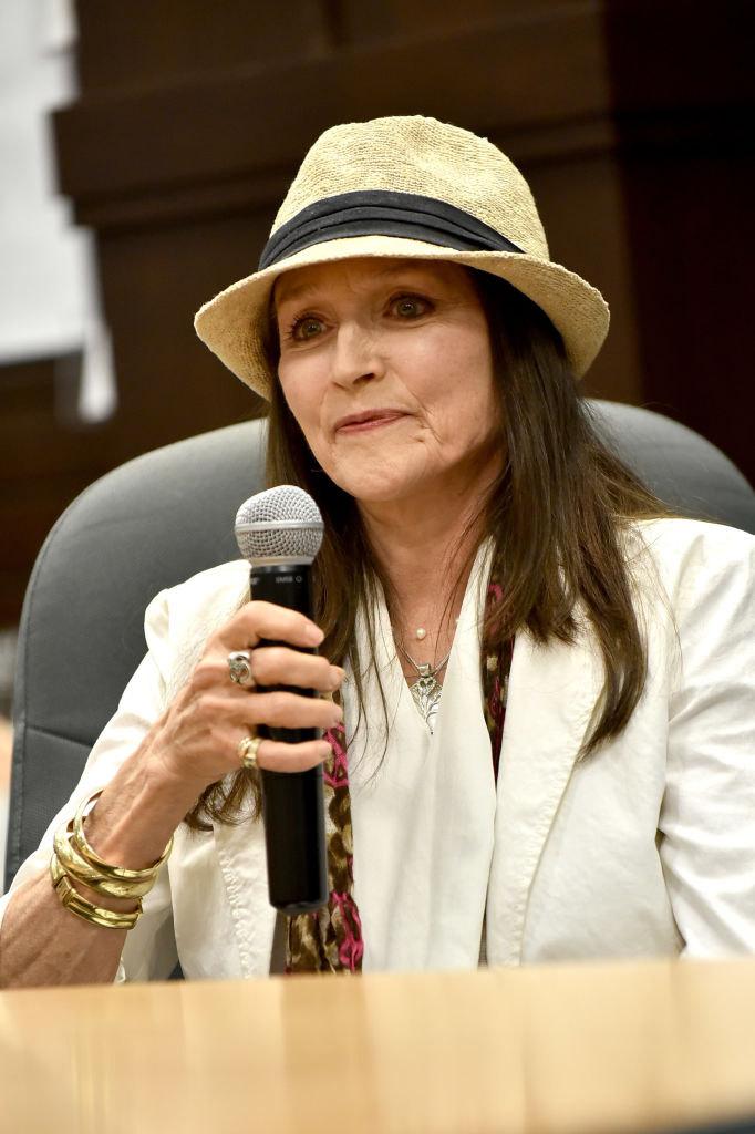 Η ηθοποιός Ολίβια Χάσεϊ με καπέλο και λευκό σακάκι.