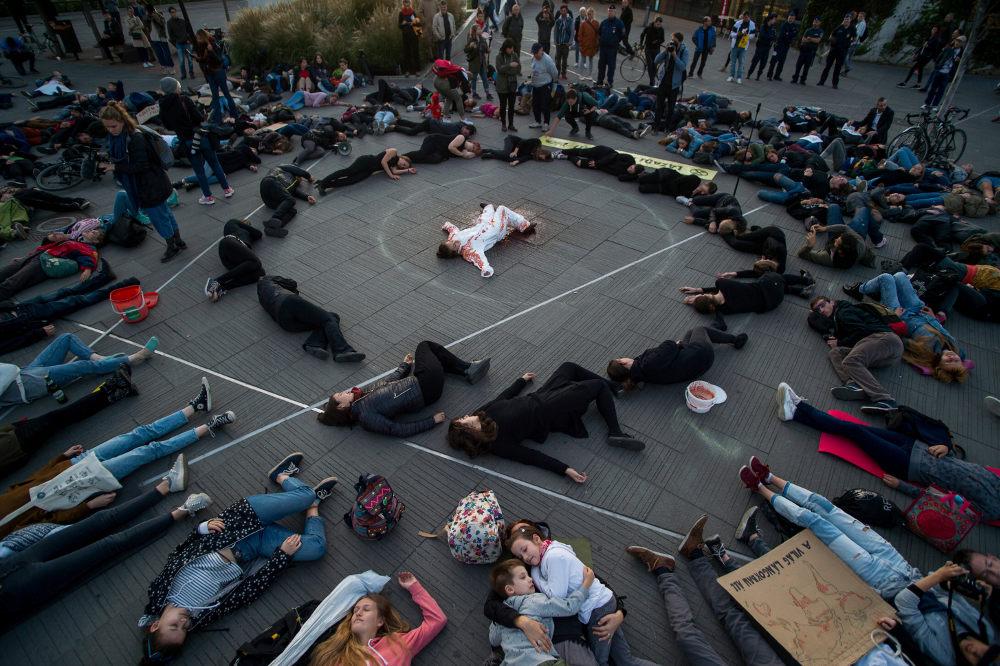 Μαθητές με τους γονείς τους ξαπλώνουν στο έδαφος «βαμμένοι με αίμα» σε μια διαμαρτυρία για την κλιματική αλλαγή / Φωτογραφία: AP Photos