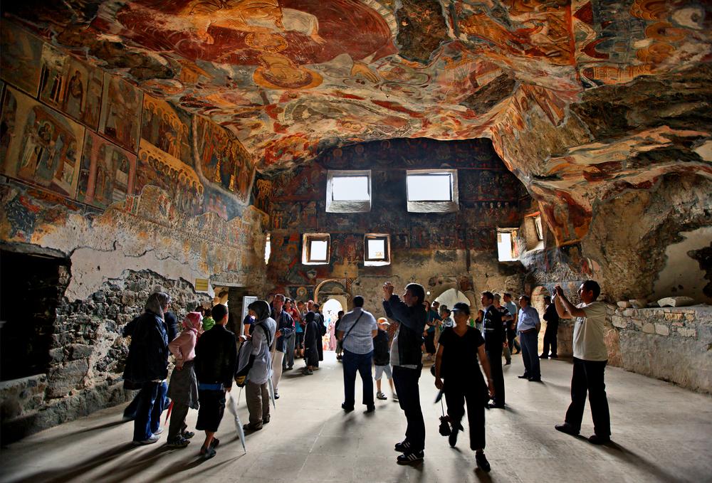 Στο εσωτερικό της Παναγίας Σουμελά στον Πόντο τουρίστες φωτογραφίζουν τις αγιογραφίες του ναού