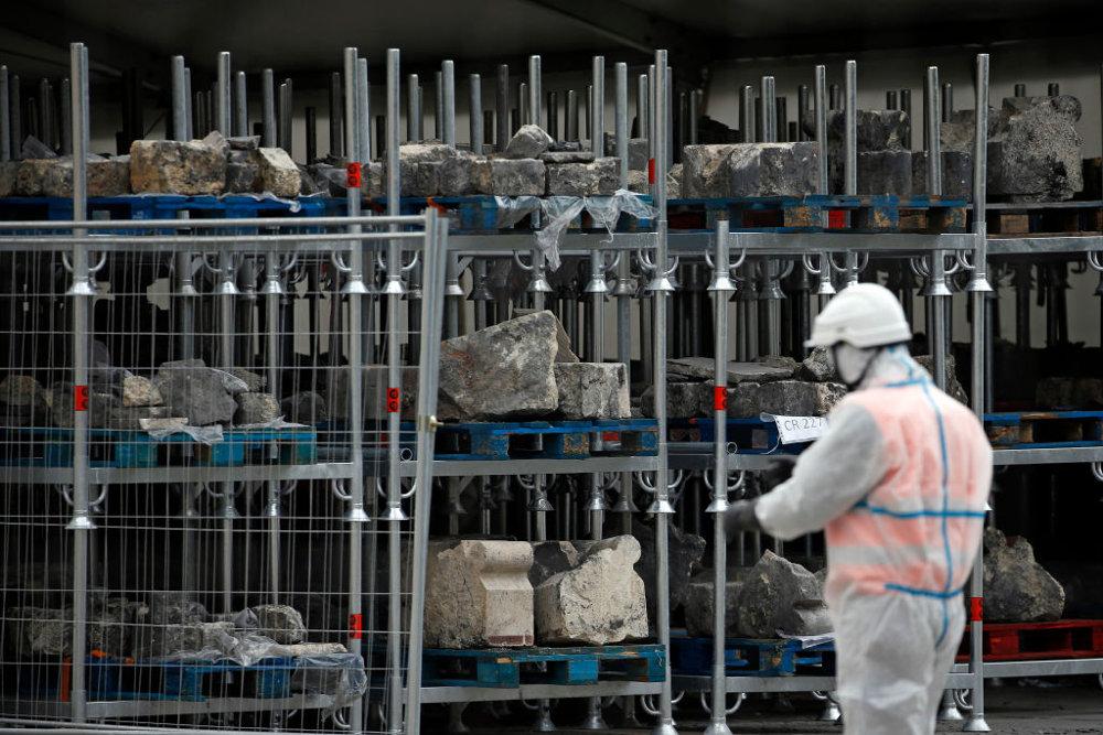 Εργάτες συγκεντρώνουν πέτρες και συντρίμμια από την Παναγία των Παρισίων όσο ξεκινούν δειλά - δειλά οι εργασίες αποκατάστασης
