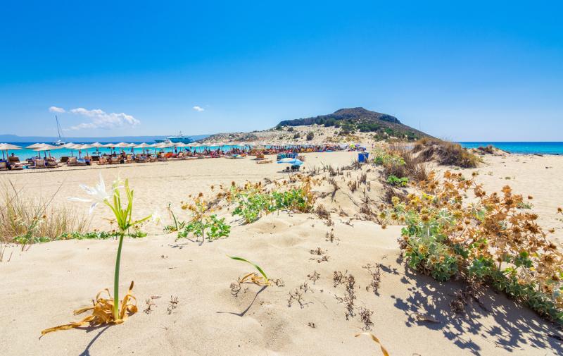 Χρυσή άμμος και στο βάθος η παραλία Σίμος