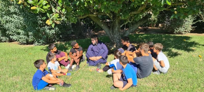 Ο πάτερ Αντώνιος κάθεται στο γρασίδι με παιδιά