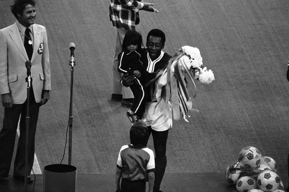 Ο Πελέ κρατά ένα παιδί στην αγκαλιά του και ανθοδέσμες τη βραδιά που σημείωσε το τελευταίο γκολ της καριέρας του