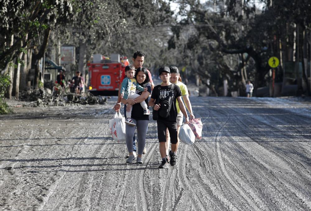 Οικογένεια περπατά σε δρόμο με στάχτες