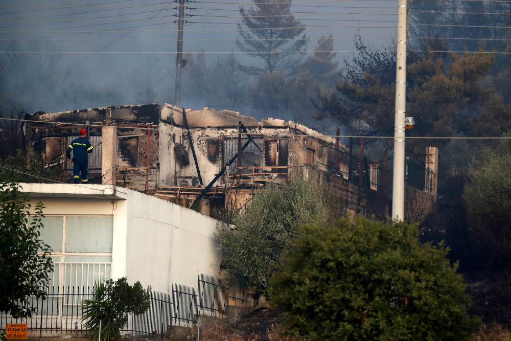 Πυροσβέστης επιθεωρεί κατεστραμμένο σπίτι