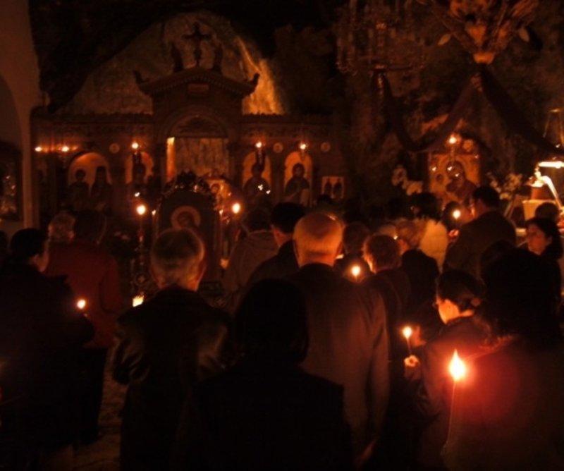 Πιστοί με κεριά κατά τη διάρκεια λειτουργίας
