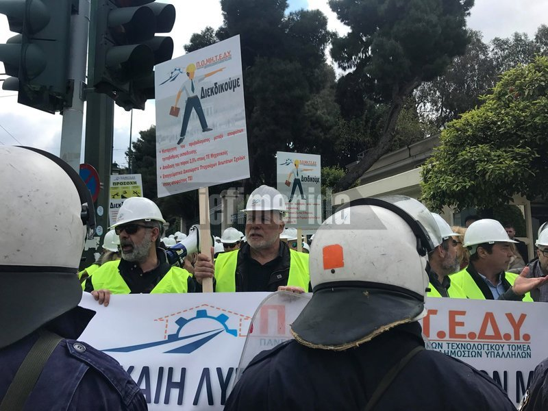 Μηχανικοί κρατούν πλακάτ μπροστά από αστυνομικούς
