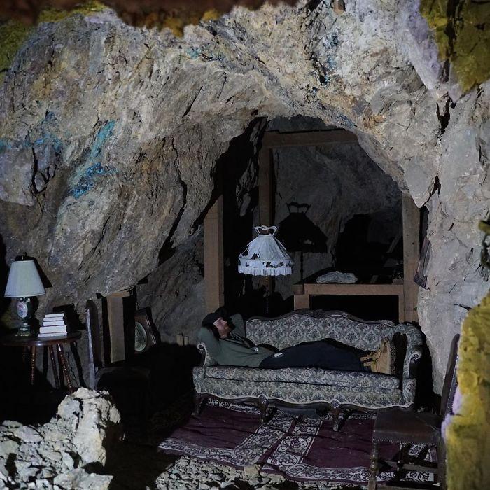 Άνδρας ξαπλώνει σε παλιό καναπέ μέσα σε σπηλιά