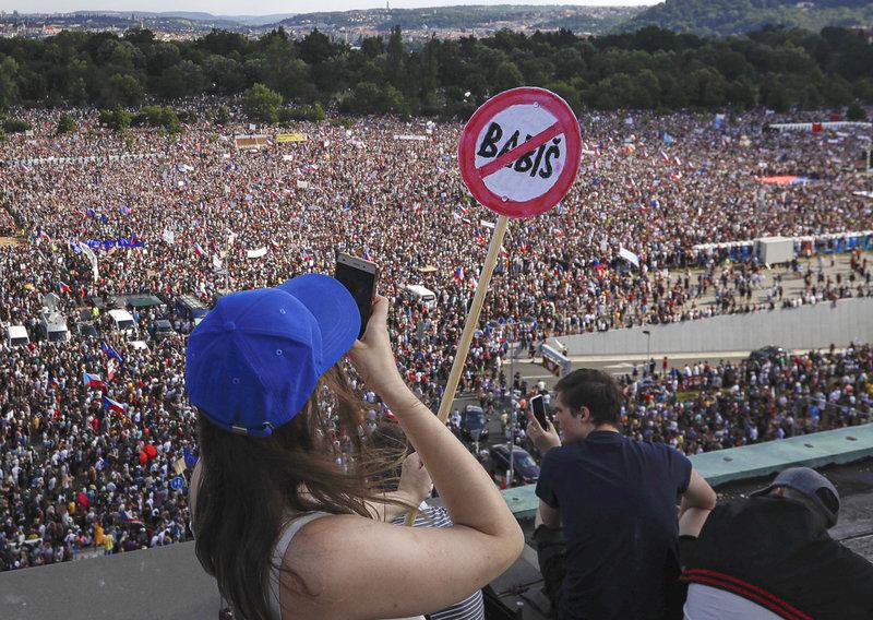 Οι διαδηλωτές κρατούσαν πλακάτ που έγραφαν «Παραιτήσου» και «Ως εδώ» και σημαίες της Τσεχίας και της Ευρωπαϊκής Ενωσης.