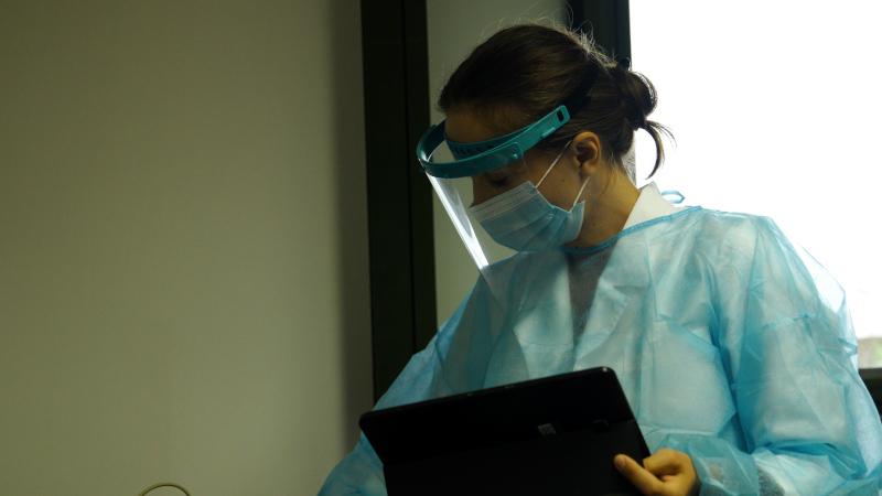 νοσοκόμα με προστατευτική στολή και υπολογιστή