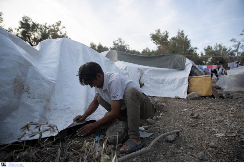 Η στιγμή που πρόσφυγας στο Κέντρο Υποδοχής και Ταυτοποίησης στη Μόρια ετοιμάζει την σκηνή του προκειμένου να προφυλαχθεί από την κακοκαιρία.