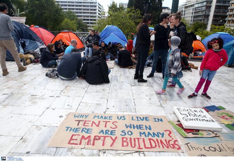 «Γιατί μας έχουν να μένουμε σε σκηνές όταν υπάρχουν τόσα άδεια κτίρια;» λέει το πρόχειρο πλακάτ -Φωτογραφία: Intimenews/ΣΤΕΦΑΝΟΥ ΣΤΕΛΙΟΣ