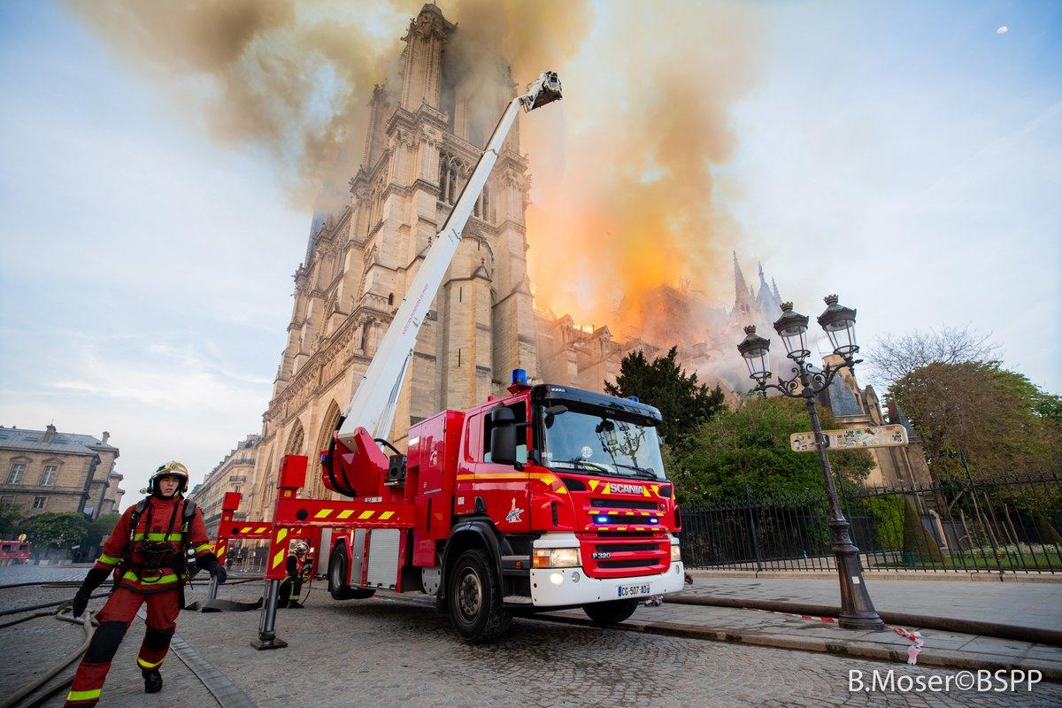Όχημα της πυροσβεστικής και πυροσβέστης μπροστά στην φλεγόμενη Παναγία των Παρισίων