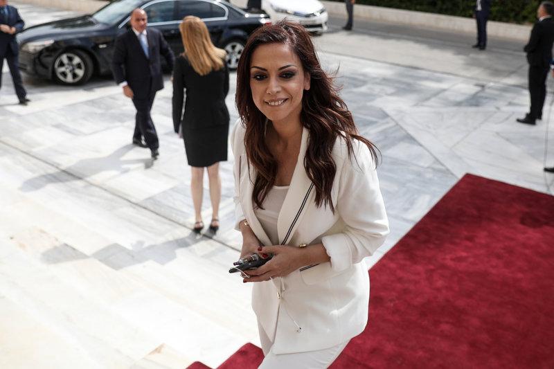 Φορώντας λευκό κοστούμι και χαμογελαστή μπήκε στο κτίριο της Βουλής