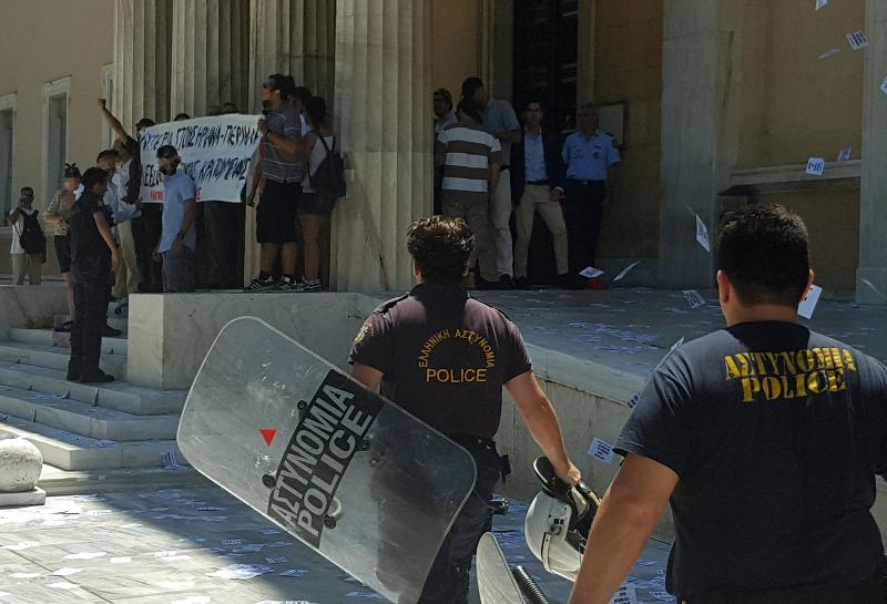 Ιούλιος 2017, μέλη του Ρουβίκωνα με πανό στην είσοδο της Βουλής. Με τα κράνη στο χέρι σε χαλαρούς ρυθμούς τους πλησιάζουν οι αστυνομικοί
