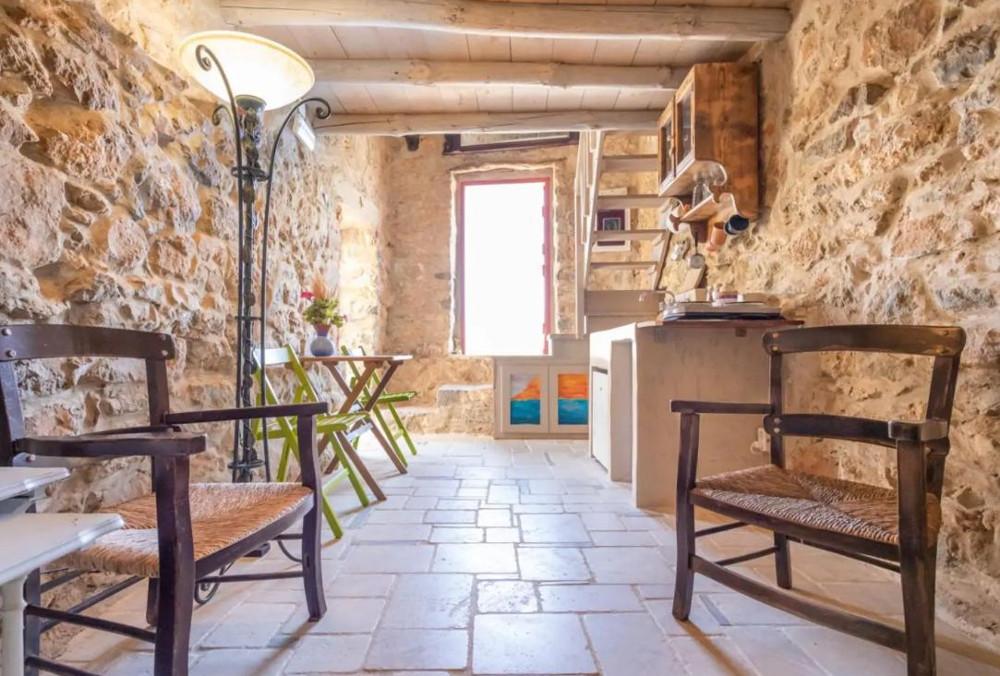 Η ρουστίκ και πολύ απλή κουζίνα περιλαμβάνει έναν μόνο πάγκο με νεροχύτη, μερικά ντουλάπια και λίγες καρέκλες