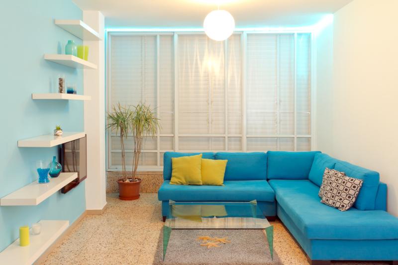 τακτοποιημένο σαλόνι με μπλε καναπέ