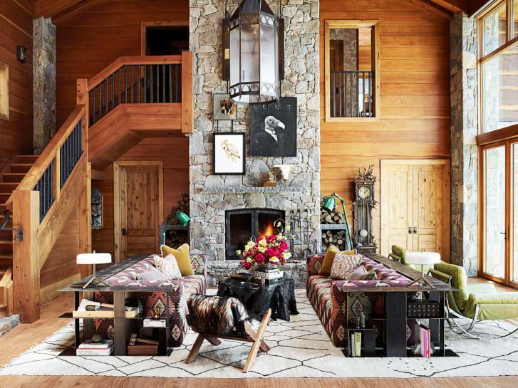 Ένας ζεστός χώρος με τεράστιους πολύχρωμους καναπέδες και χάλκινες βιβλιοθήκες δίπλα σε ένα πελώριο πέτρινο τζάκι