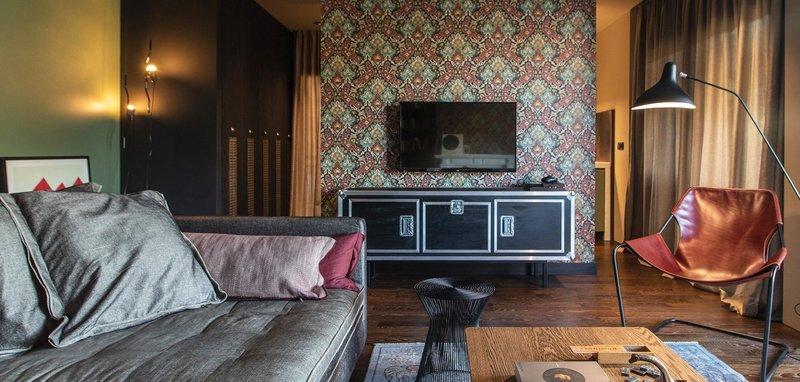 Η τηλεόραση σε έναν τοίχο με floral ταπετσαρία, ένας γκρι καναπές και μια καρέκλα
