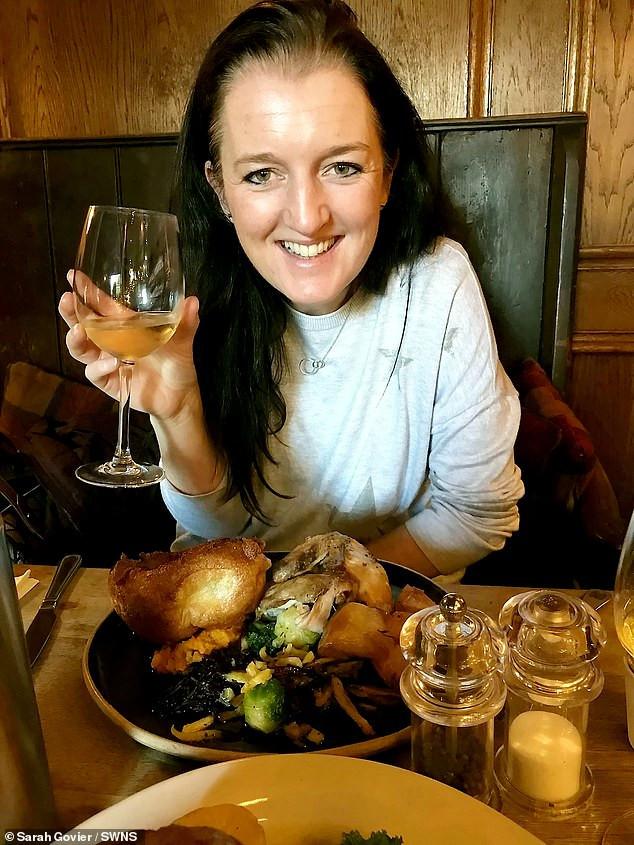 γυναίκα απολαμβάνει φαγητό με ένα ποτήρι κρασί