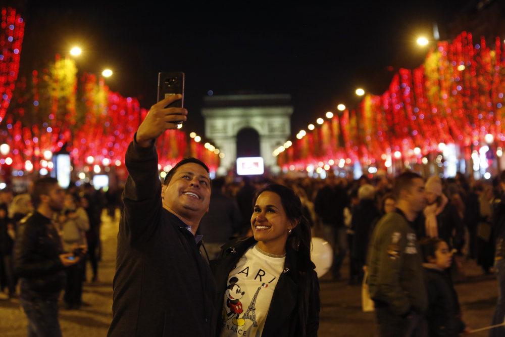 Ζευγάρι βγάζει σέλφι με φόντο την αψίδα του θριάμβου στο Παρίσι, με αφορμή την φωταγώγηση της Champs Elysees