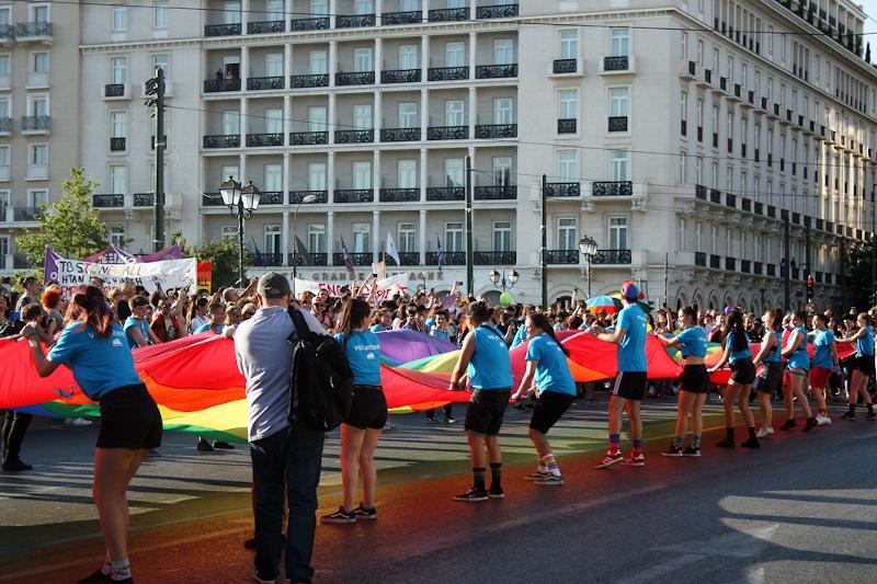 κόσμος κρατά μεγάλη σημαία ΛΟΑΤΚΙ+ κοινότητας στο Σύνταγμα