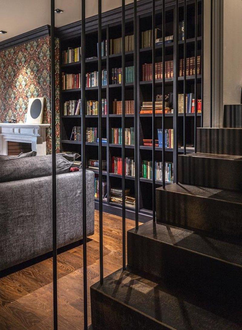 Σκάλα σε πρώτο πλάνο και μια βιβλιοθήκη και ένας καναπές από πίσω